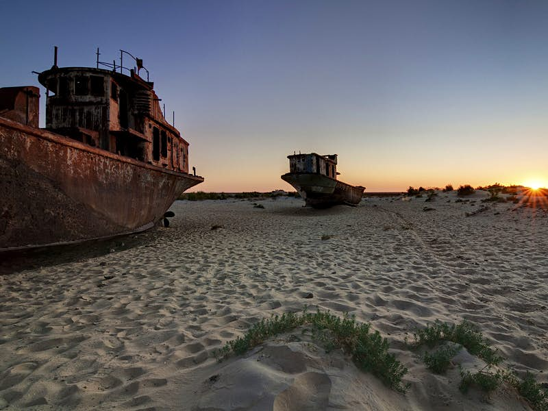 Rusting ships beached on sand with the sunset behind.