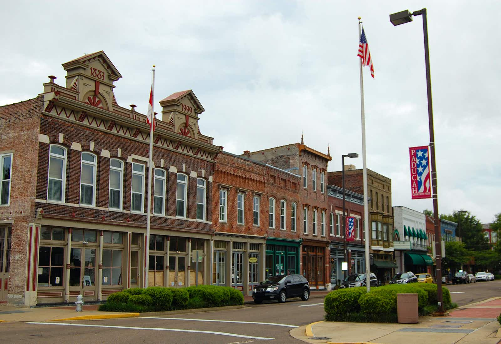 Angle shot of 19th-century commercial brick buildings lining the main street of Paducah, Kentucky, with an American flag in the foreground and clouds overhead