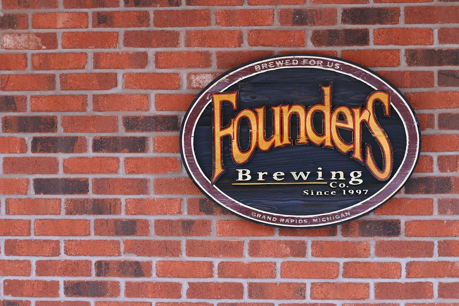 Red brick wall with oval sign containing Founders Brewing Co logo: Yellow curving words in a serif font on a green background. The number of craft breweries continues to grow in the United States.