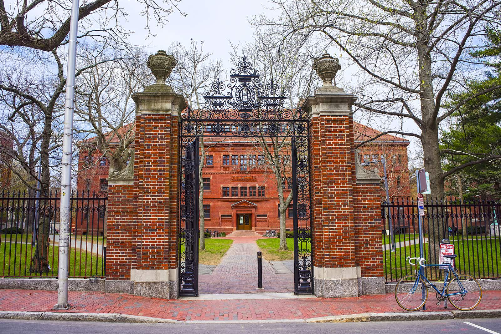 red brick gateposts and wrought iron, open gate leading to a redbrick residence hall at Harvard on a sunny day