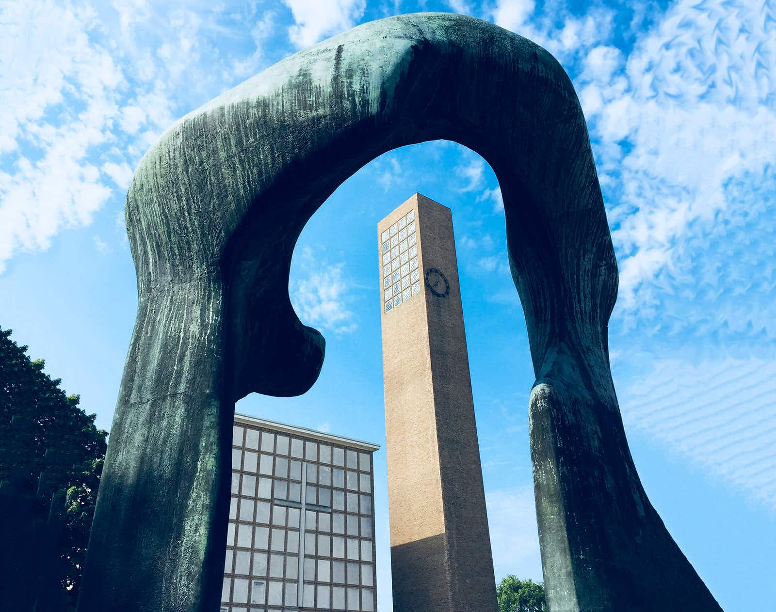 A mid-century modern church bell tower is framed by a blue abstract sculpture by Henry Moore in Columbus Indiana on a sunny day