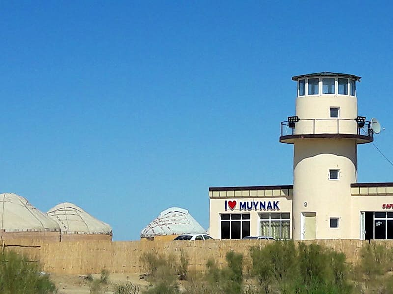 A white, round lighthouse stands next to a small building and several round yurt tents.