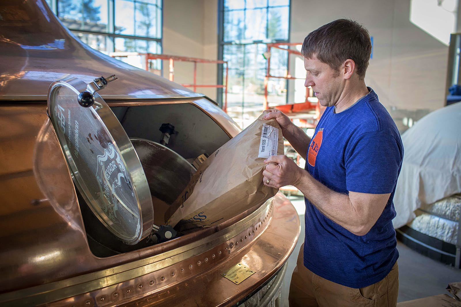 Man in blue shirt pours a sack of oats into an opening ina an old-fashioned copper still as part of the beer-making process. Craft breweries around the country take its products seriously.