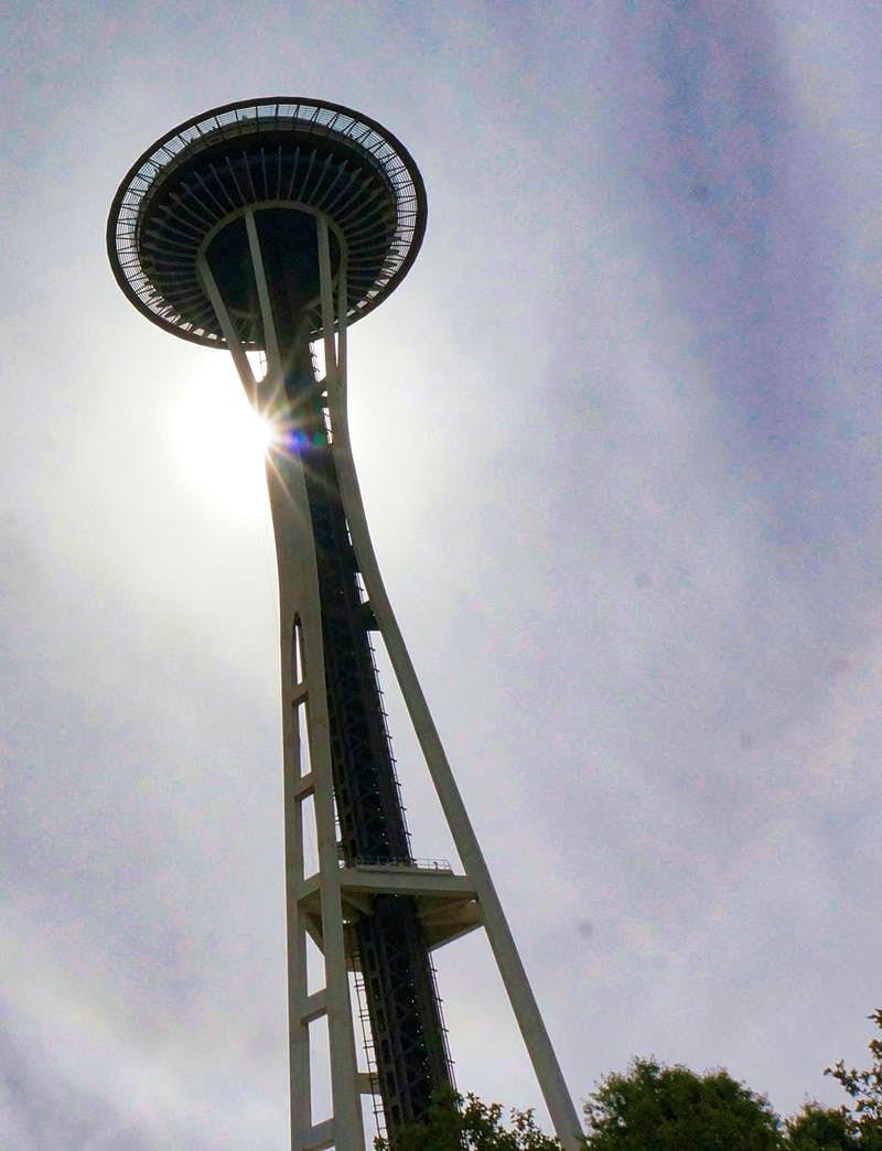 A setting sun casts the Space Needle into profile as it drops behind the tripod tower and disc-shaped observation deck © Valerie Stimac / Lonely Planet