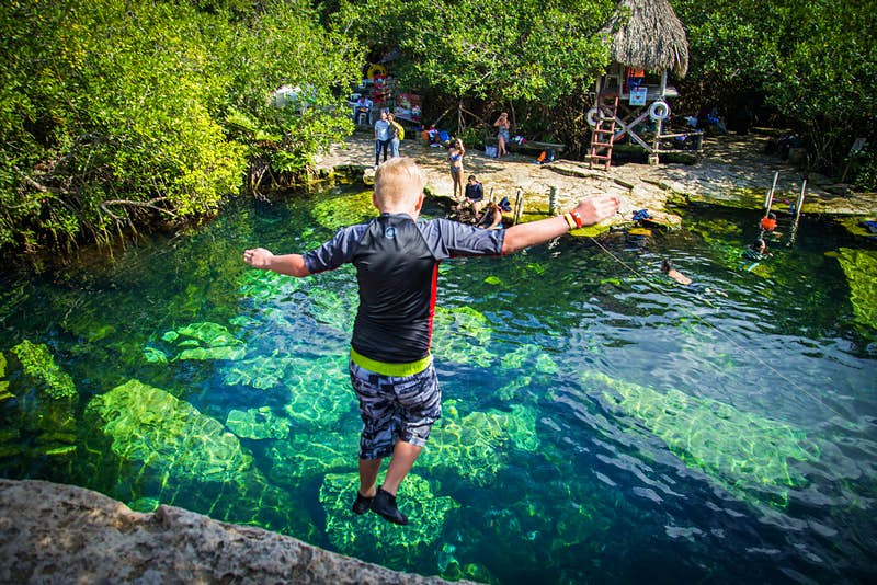 A boy jumps off a ledge into clear deep water