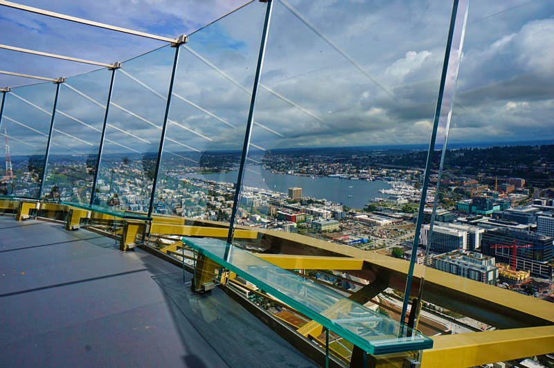 Curved glass panels surround an observation deck hundreds of feet in the sky as the city unfolds beyond