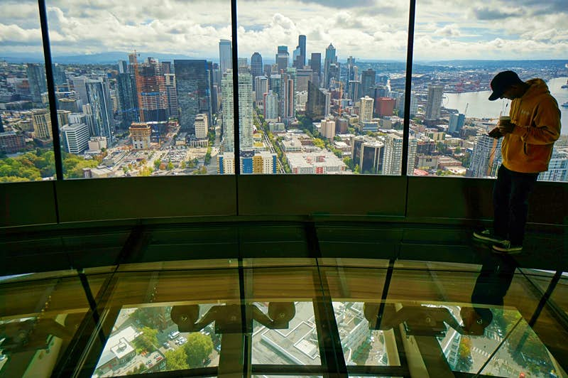 A man takes a picture with his camera phone through the clear glass floor of the Space Needle