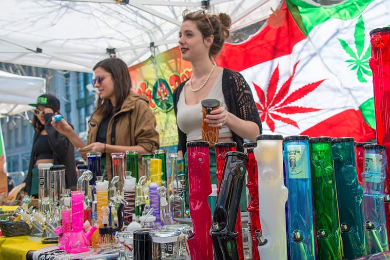 Two women sell bongs and other marijuana items at an outdoor stall, with a flag of Canada in the background that has the maple leaf replaced with a marijuana leaf.