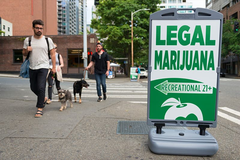 People pass a Legal Marijuana shop sign late in the day in Seattle, Washington