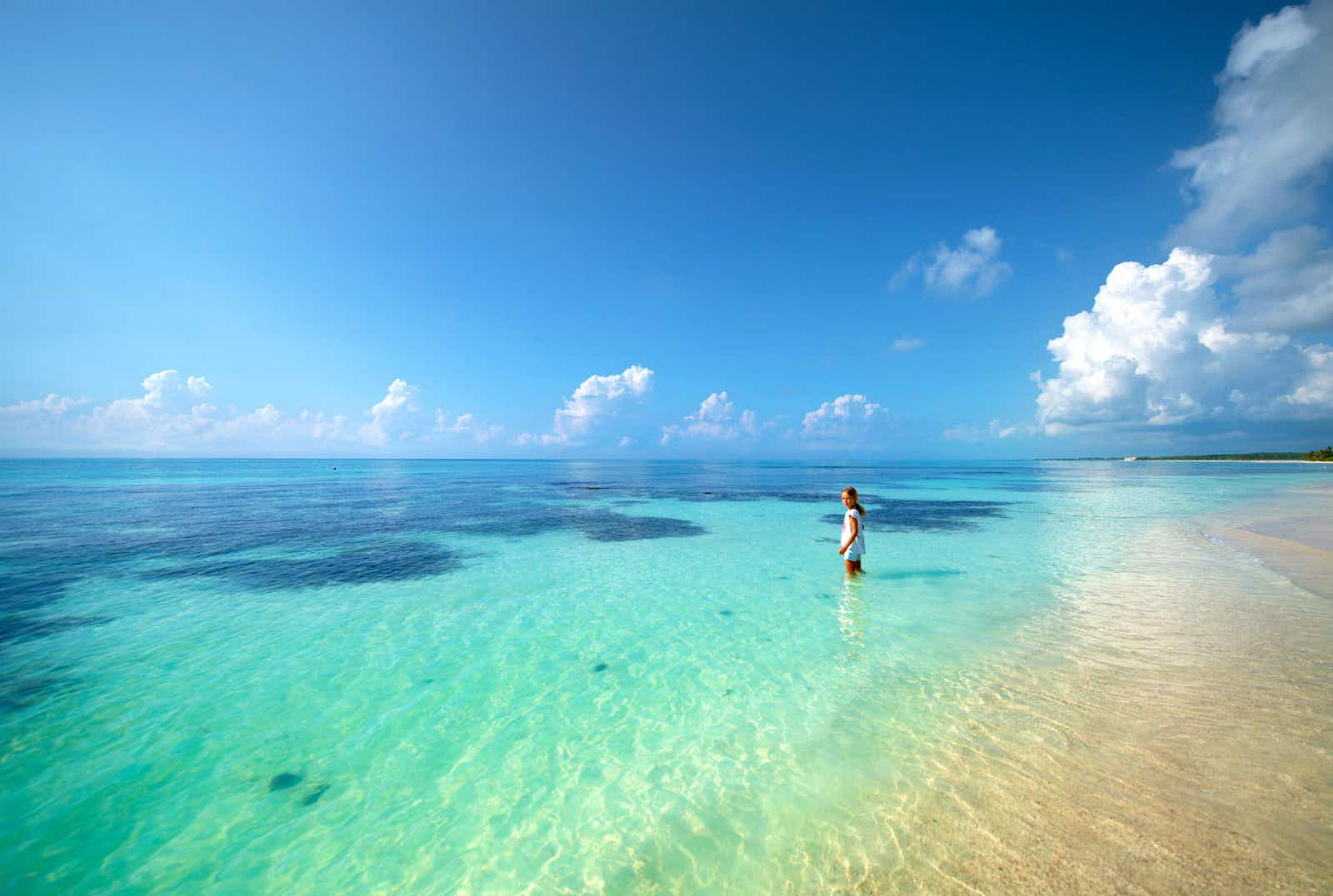 A girl stands in the shallow water of a turquoise ocean