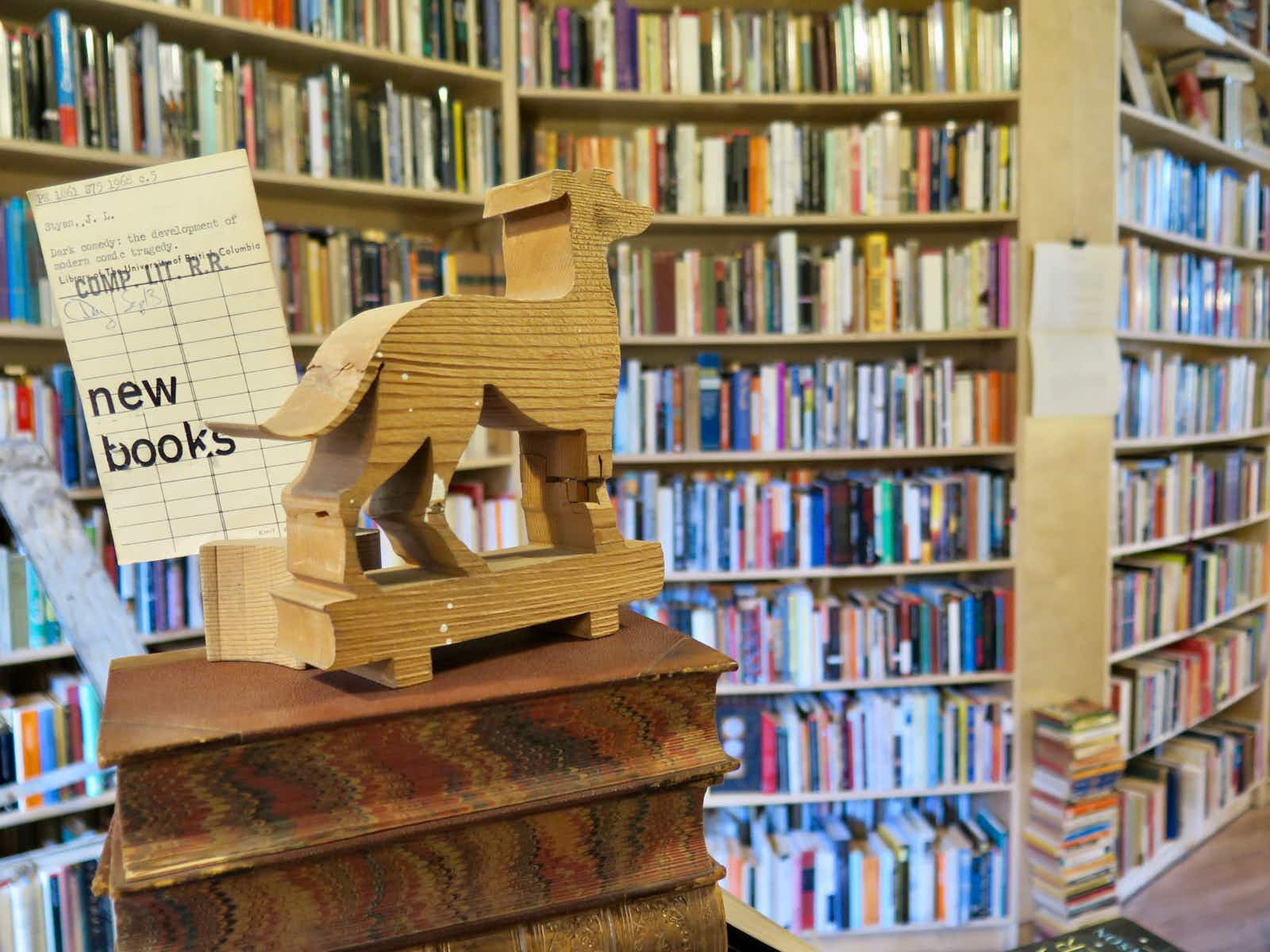 Books and a dog-shaped wooden carving inside the Paper Hound, Vancouver