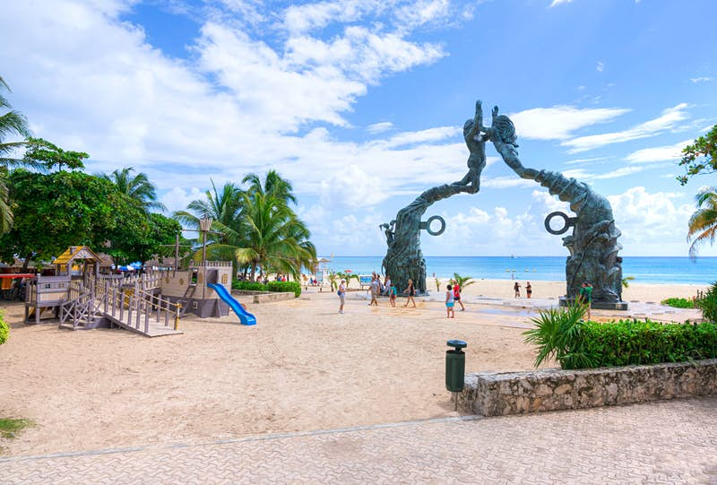 A mermaid statue serves as a gate to a pirate-themed playground on the beach