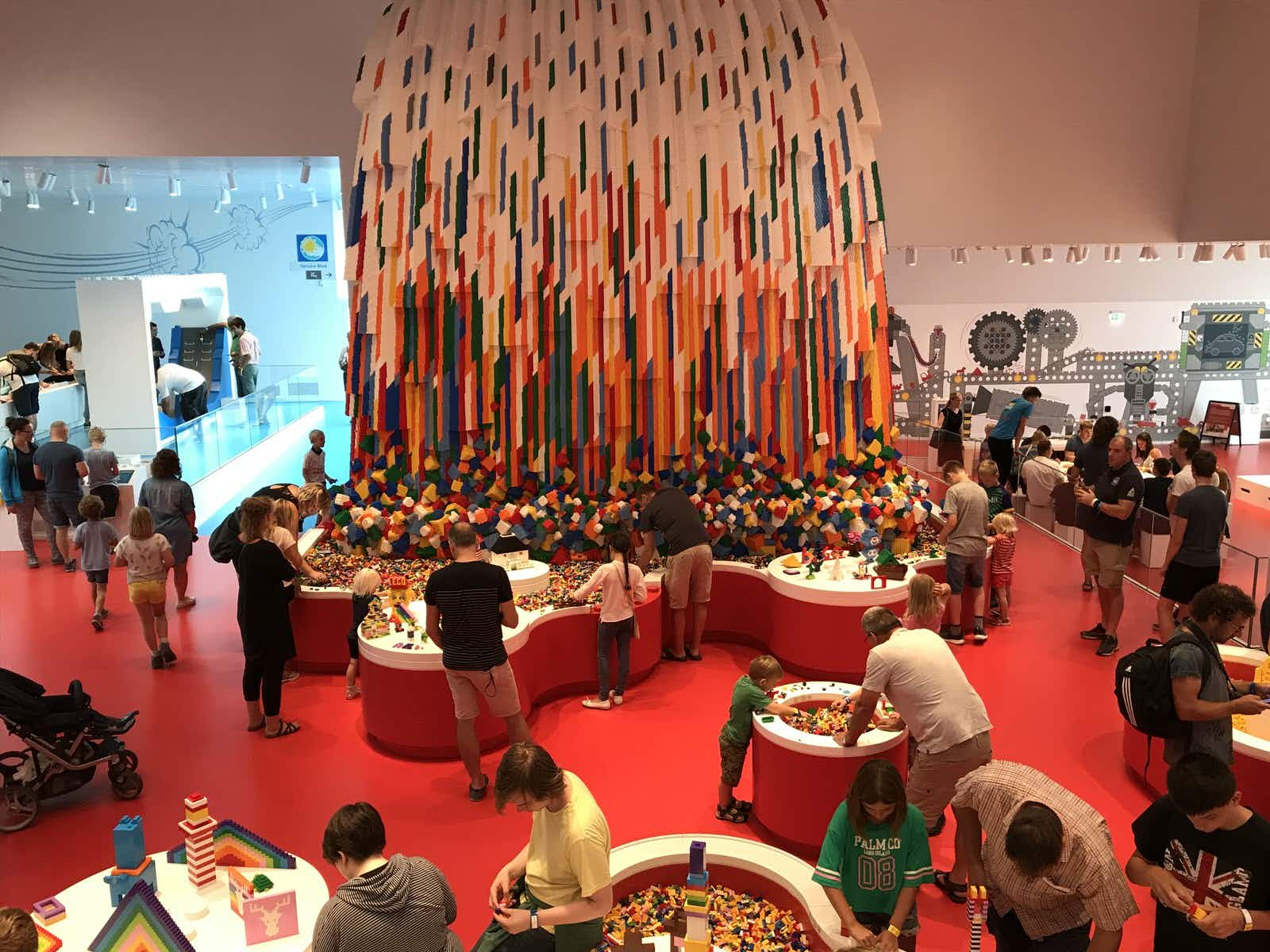 Adults and children playing with brightly-coloured Lego bricks inside the Lego House in Billund © Abigail Blasi / Lonely Planet