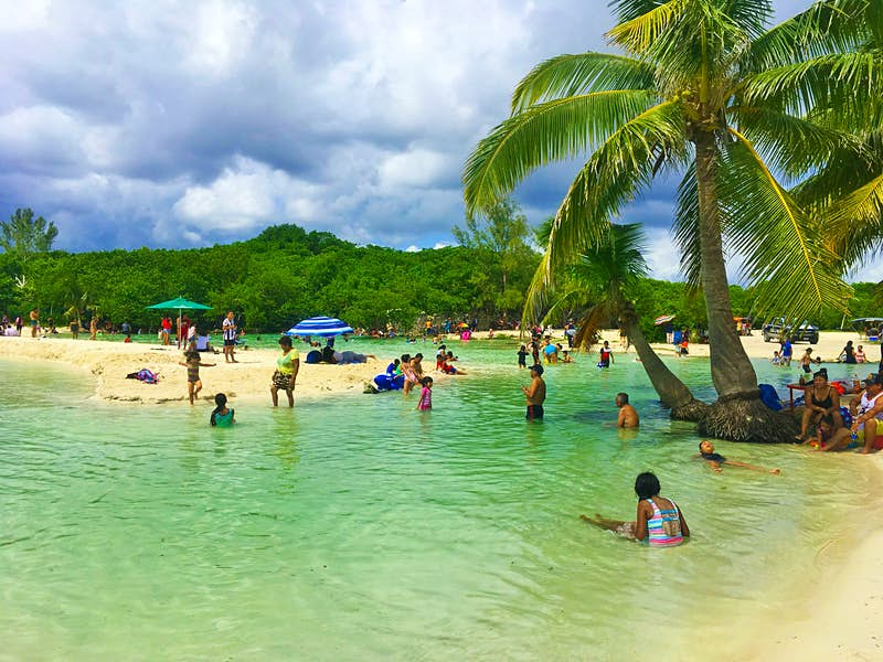 People enjoy the shallow water and white sand beach under palm trees