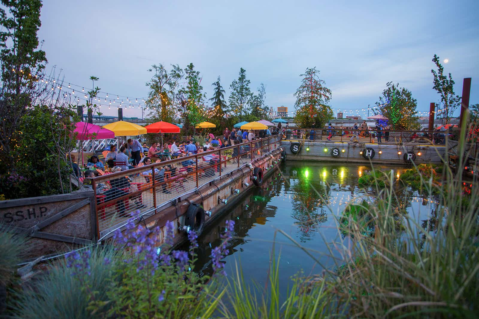 Long shot of park set up on docs on a river with red and yellow umbrellas over tables