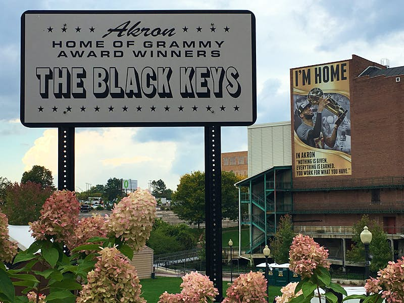 """Sign reading """"welcome to Akron Ohio, home of the Black Keys' surrounded by hydrangeas with a stadium in the background"""