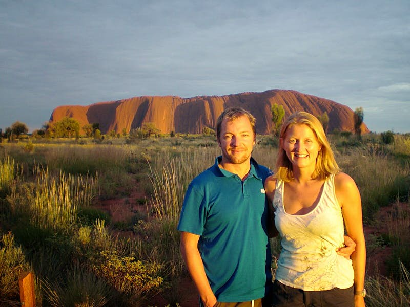 James and his partner pose in front of Uluru, Australia.