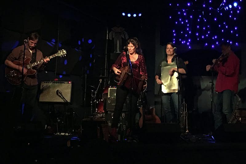 A man with a guitar, a woman singing, a woman with a washboard and a man on a flute perform music on stage in a dark club