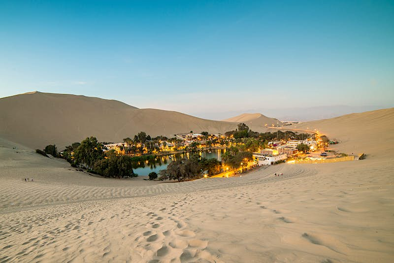 The desert oasis of Huacachina at dusk. The small body of water is surrounded by bushy green trees, white buildings and lights.