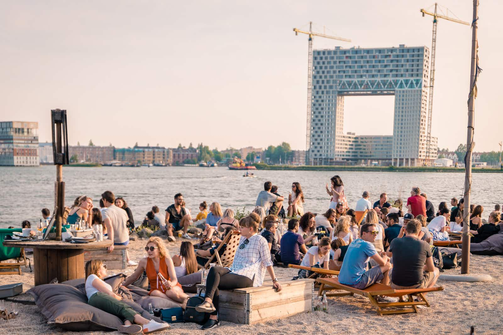 Patrons lounge on a beach at art festival Kinetisch Noord, held at NDSM Wharf