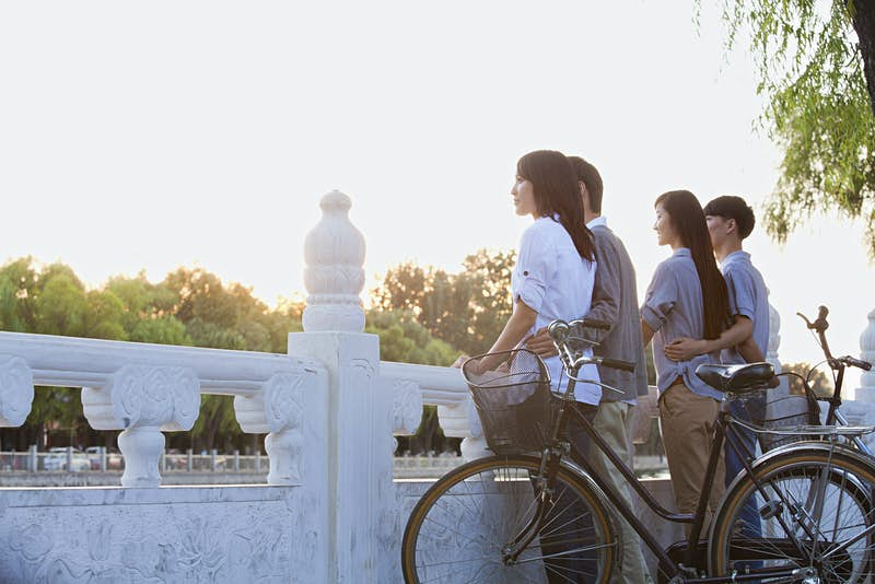 Two couples with bikes admire the view of Houhai Lake, Beijing
