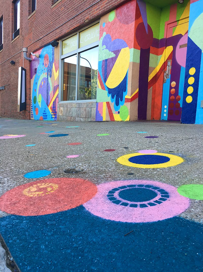 An old brick building is now covered in abstract geometric designs in yellow, blue, purple, orange and red. The sidewalk in front of building has colorful circles painted on it.