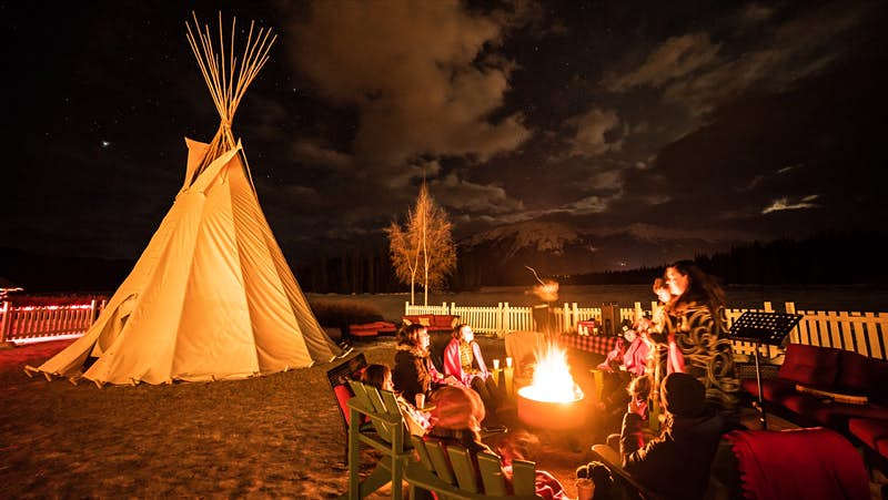 A tipi sits nearby as a group of people talk around a campfire and look up at a sky full of stars