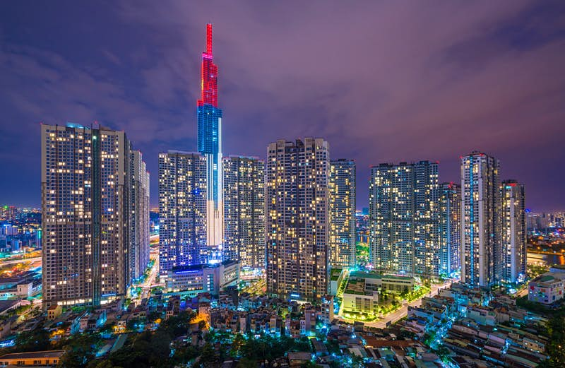 Landmark 81, pictured at night, towers above Ho Chi Minh City. The skyscraper is illuminated by white, blue and red lights in horizontal bands and surrounded by smaller, sparkling buildings.