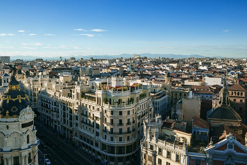 Looking down over Madrid's Gran Vía, which is full of tall handsome buildings including one in the foreground with a gilded cupola; beyond, the Madrid skyline stretches into the distance.