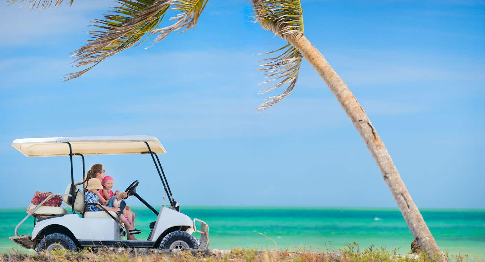a woman drives a golf cart with a young girl on her lap and a boy next to her on the beach toward a palm tree