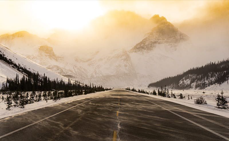 A snow-swept road is bathed in golden light as it appears to run straight into a mountain