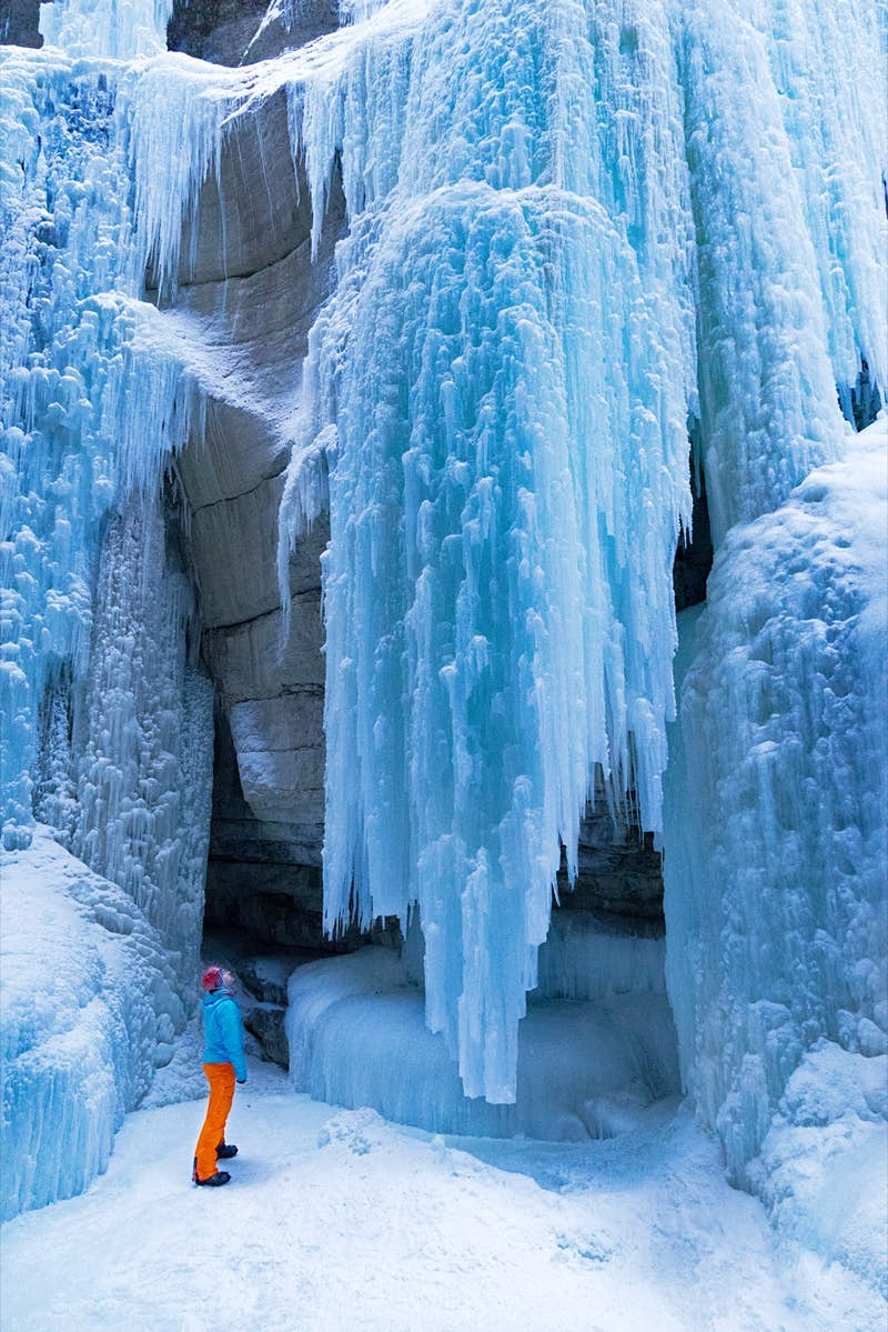 A very small looking person gazes up at a huge curtain of solid ice made from a frozen waterfall.