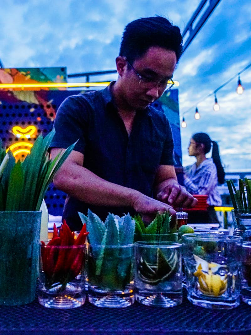 A barman mixes a 'phojito' at Anan at dusk, one of HCMC's best rooftop bars. The bar counter is lined with containers of lemons, limes and various other cocktail ingredients.