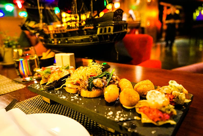 A selection of tapas served at Shri, in Ho Chi Minh City, on a slate. Including bruschetta, arancini balls and a number of other small bites. This rooftop bars has a nautical theme.