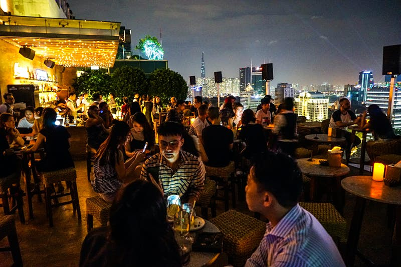 Revellers gather at Saigon Social Club's rooftop bar to drink and dine. The space twinkles with candles and fairylights as well as city lights in the background.