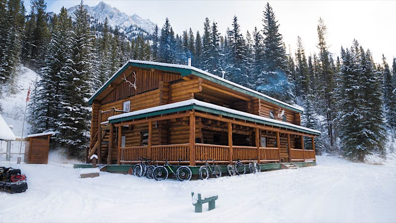 Smoke comes from the chimney of a rustic mountain lodge, with snow covered evergreens all around and fat bikes parked in front.