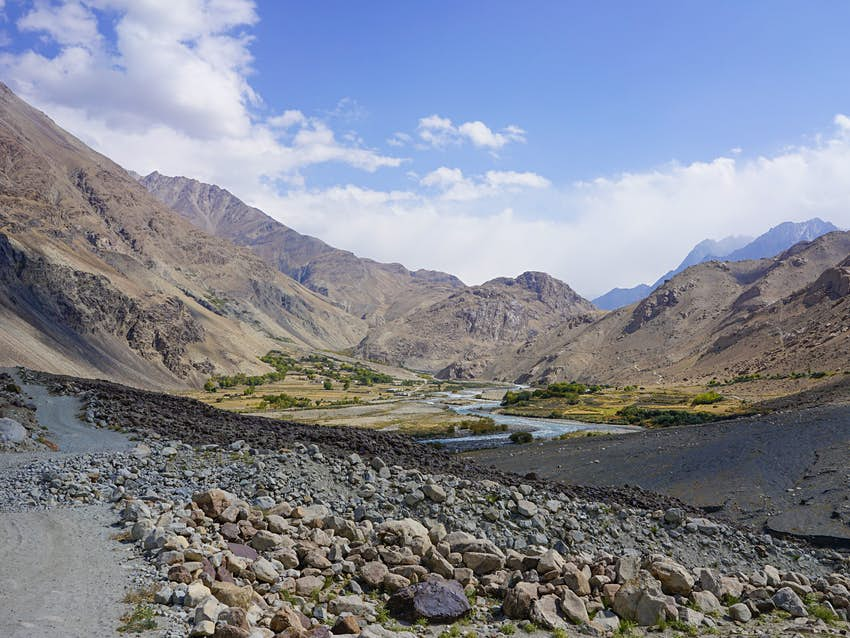 A rock-strewn landscape gives way to a river running through a dry mountain valley