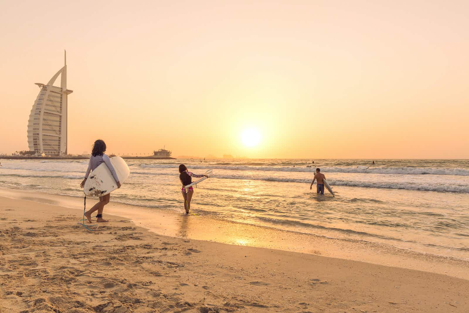 October 4 2017: Three Surfers go into the waters during sunset with the Burj Al Arab hotel in the background.