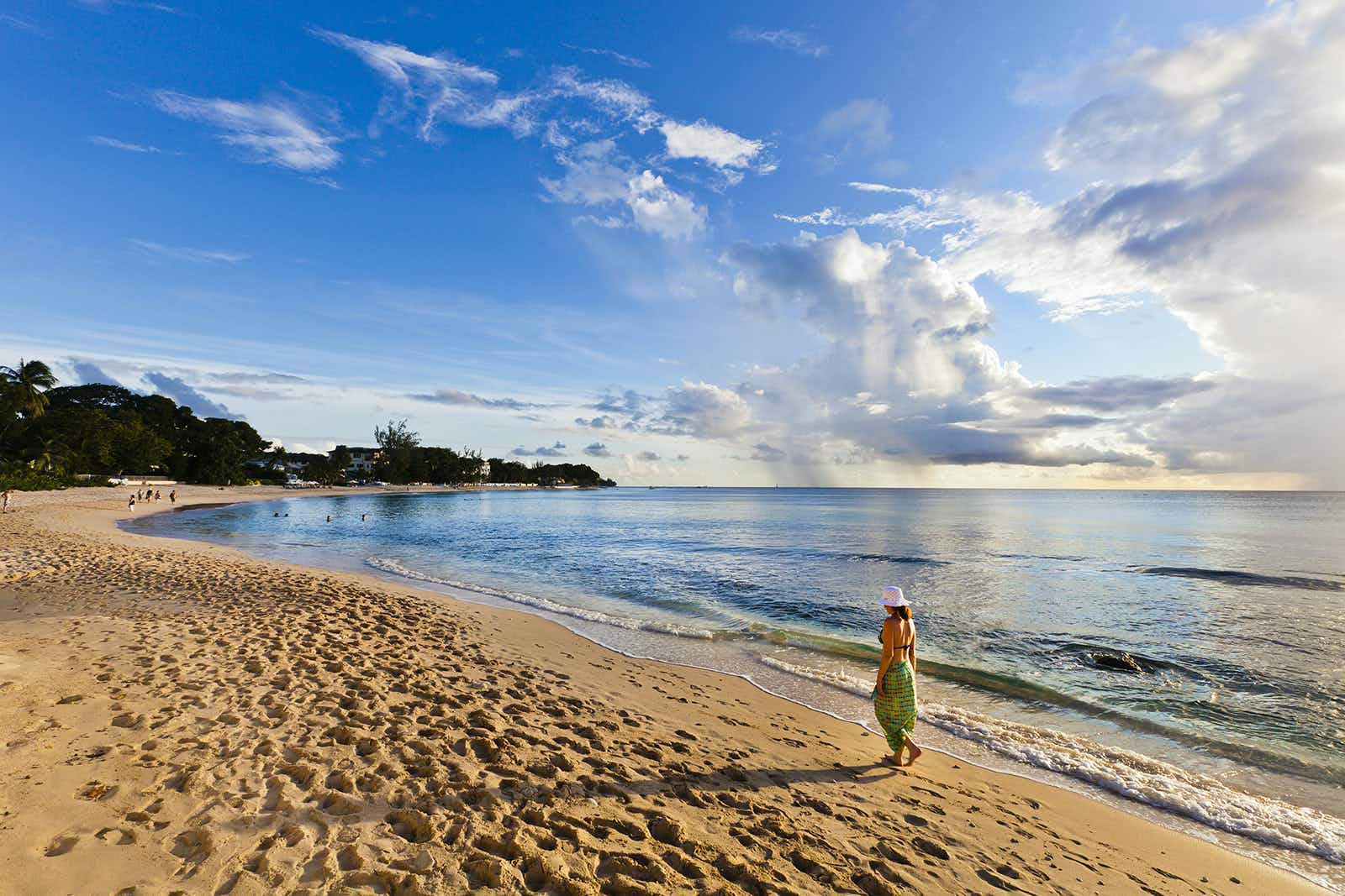Woman walking on the beach of Paynes Bay at sunset. Surrounded by a beautiful stretch of sand, this is one of the most popular beach on the west coast of Barbados. Canon EOS 5D Mark II