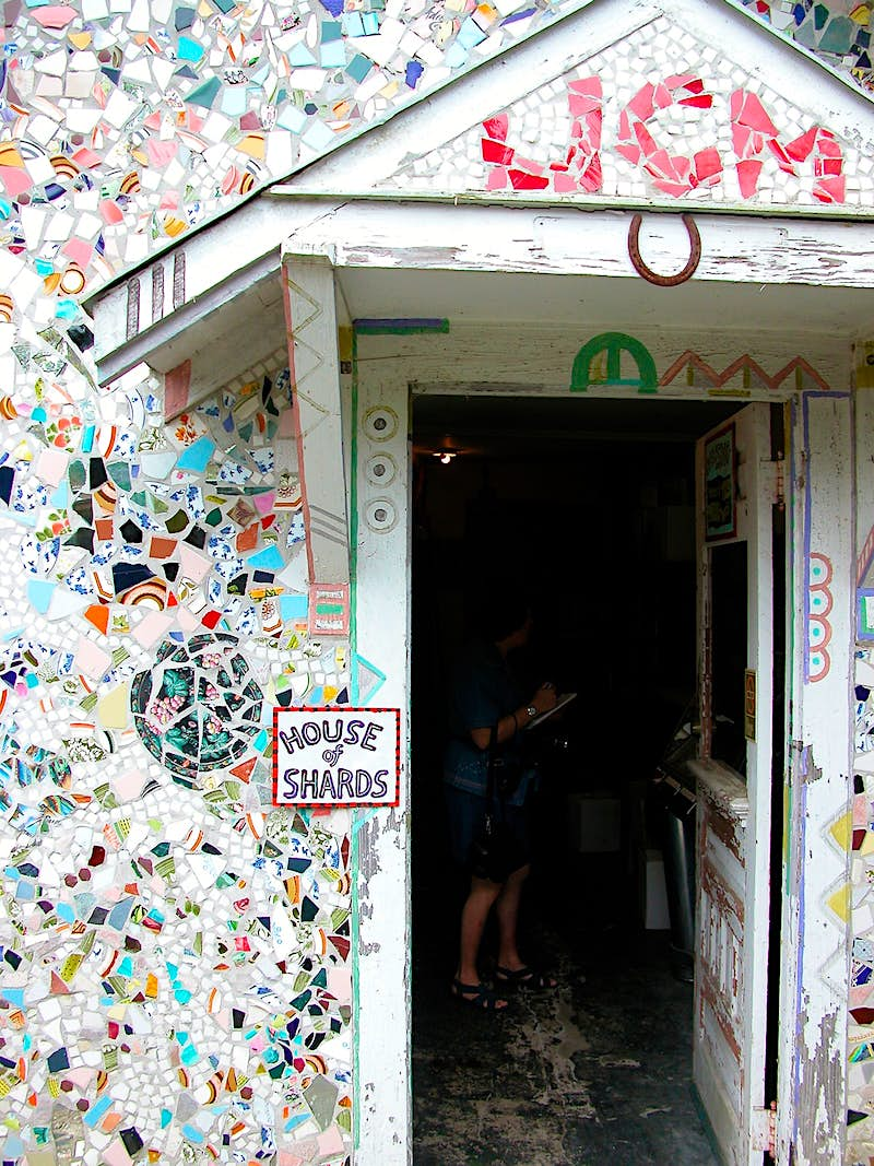 A white house covered with colorful pieces of glass. There's a sign that says 'House of Shards' right next to the door. Louisiana is filled with quirky spots.