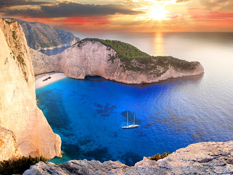 A solitary sailboat at the famousNavagio beach on the Ionian island of Zakynthos© Samot / Shutterstock