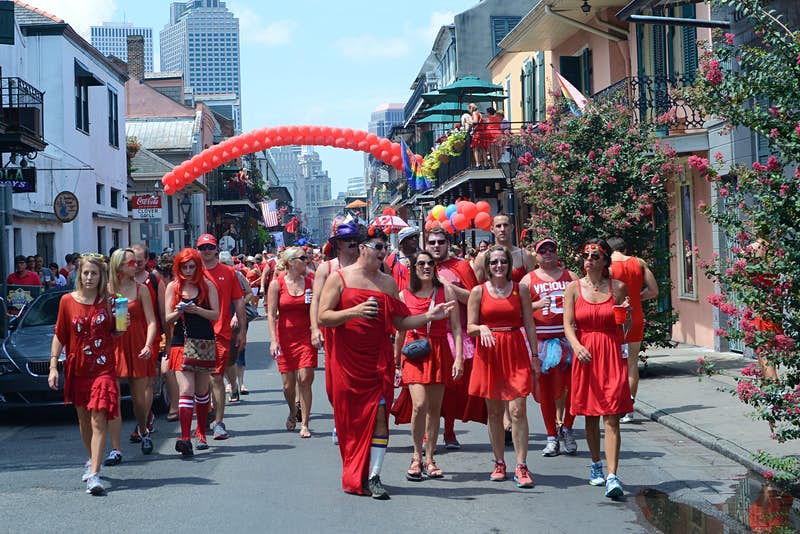A group of men and women all wearing red dresses walk down the streets of New Orleans.