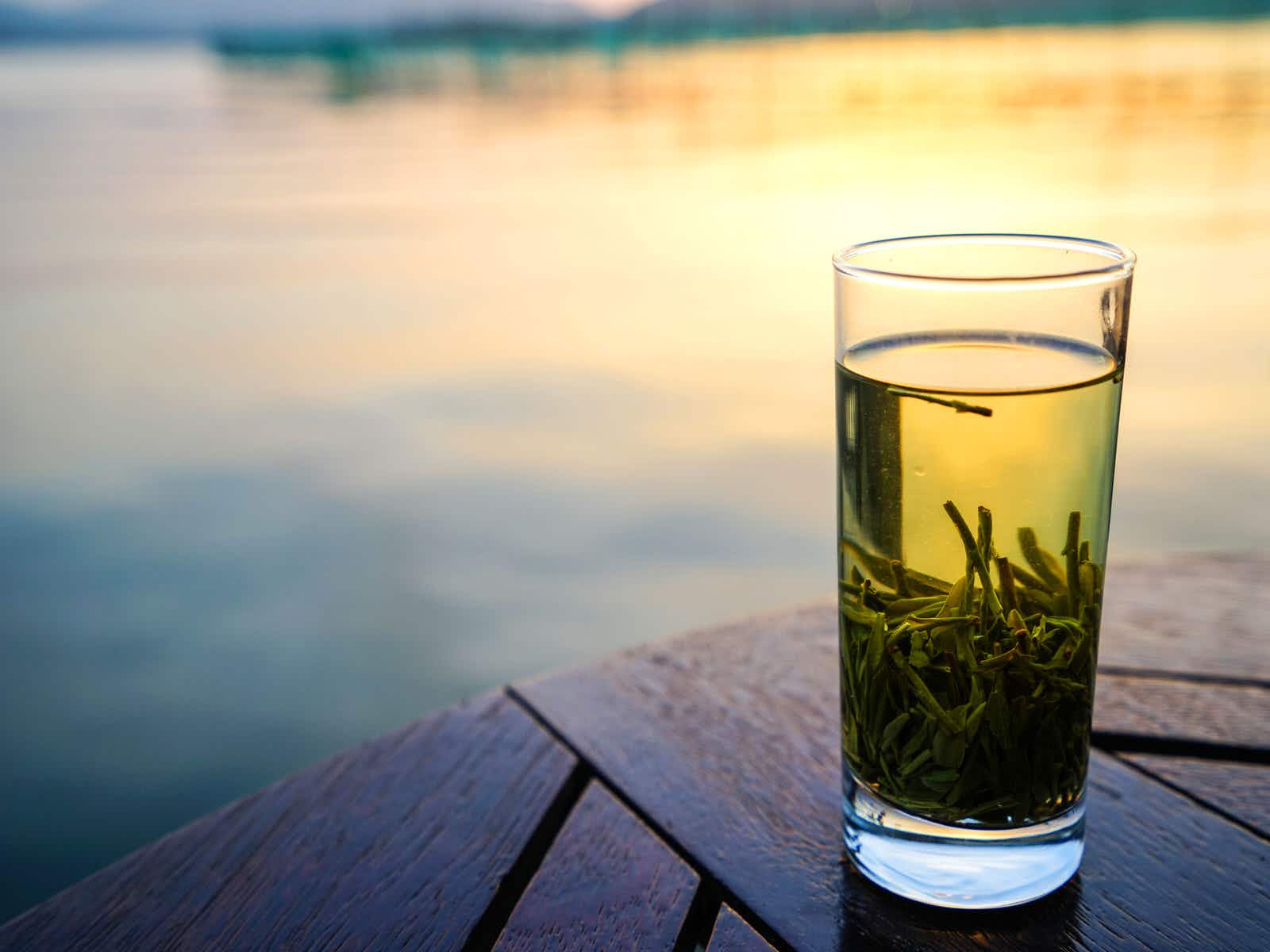 A cup of green tea settled in a tall, clear glass, with sunset reflecting in a pond in the background.