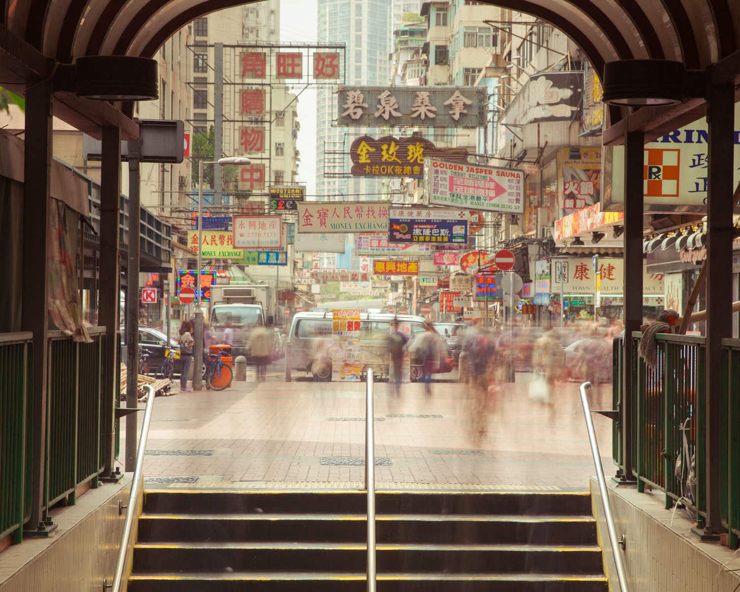 Blurred motion of people going down the stairs of underground crossing with numerous Chinese signs in the background
