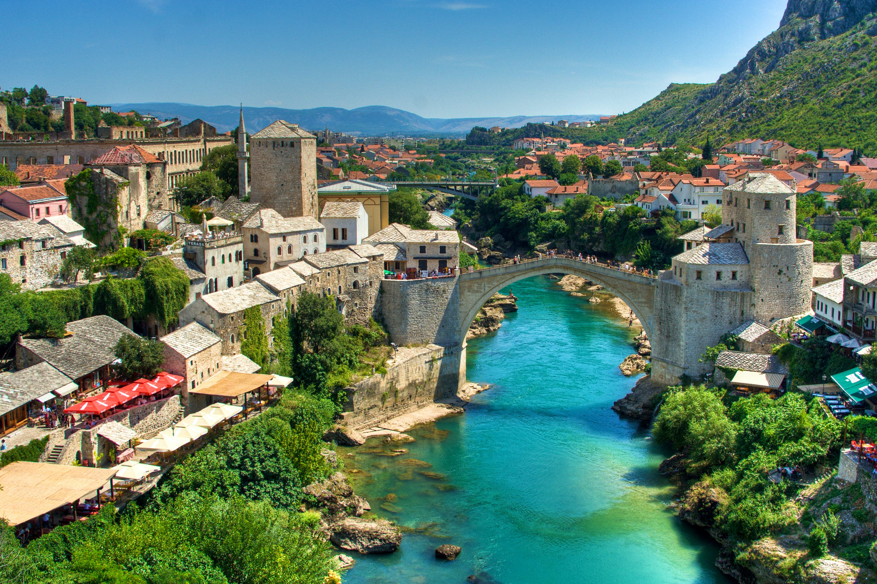 A turquoise river flows underneath an arched bridge, which connects two sides of the city of Mostar