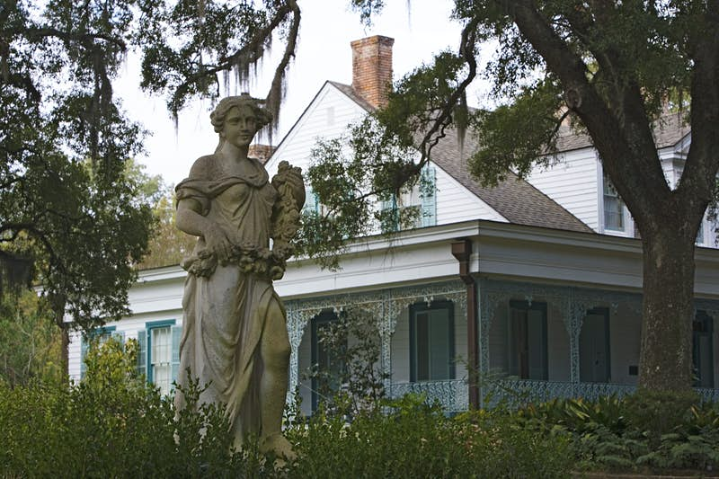 A statue of a woman holding flowers is positioned in front of a white house with light blue shutters on Myrtles Plantation in Louisiana