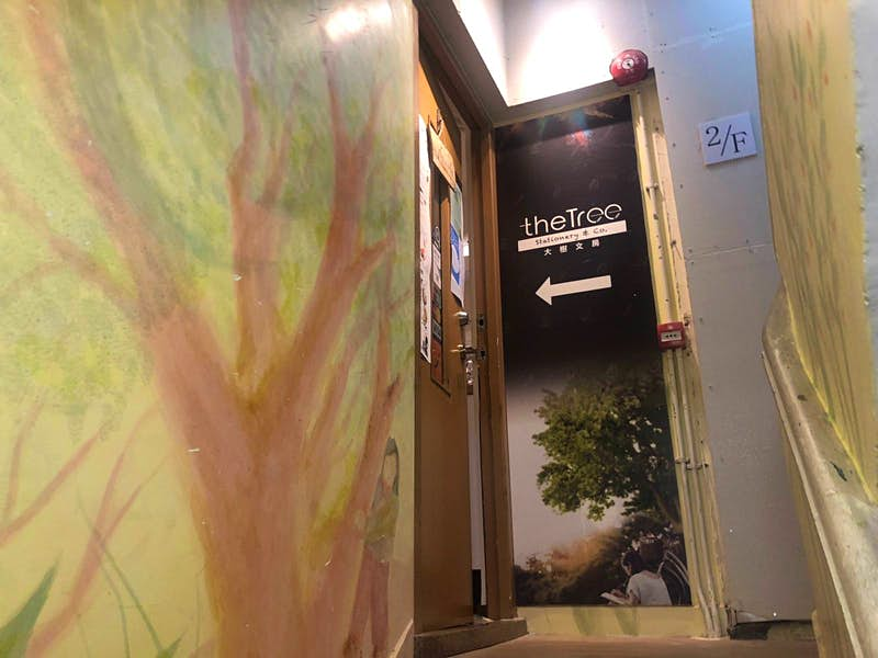 A stairwell with a mural of a tree and the Tree Stationery sign denoting entrance to the shop