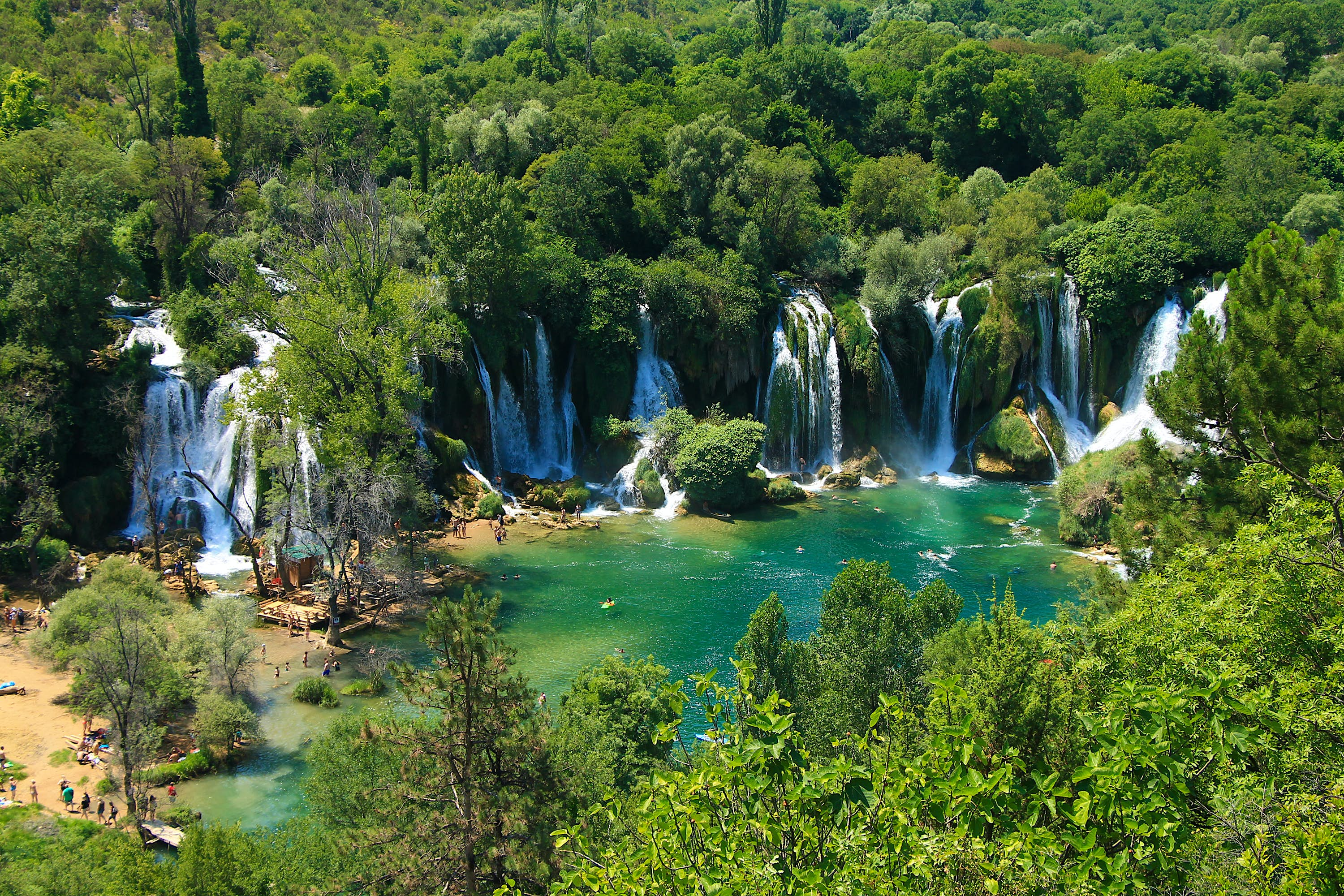 A series of waterfalls flow out of dense forest into a green-blue pool. A few people can be seen on the beach to the left.