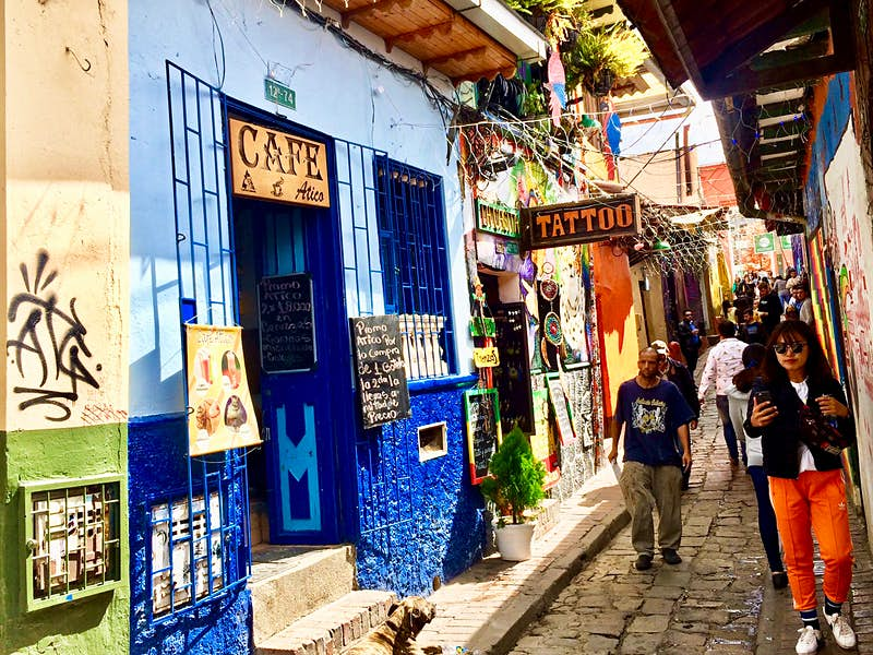People walk down a narrow cobblestoned streets with colorfully painted shops on either side
