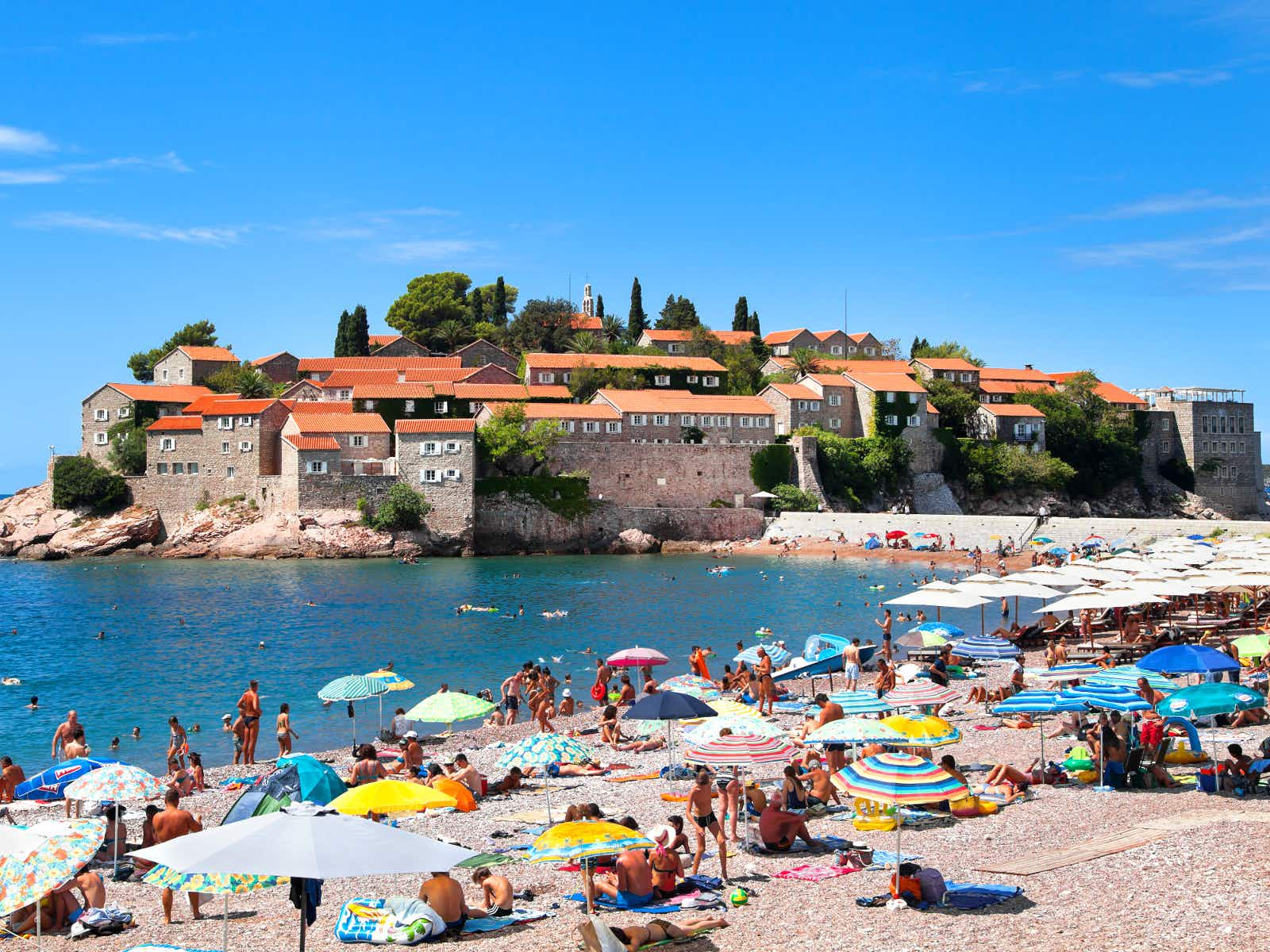 Gorgeous views of Sveti Stefan from the pinkish sands at its southern end © photosmatic / Shutterstock